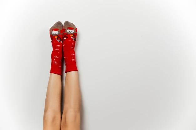 Jambe de femme en chaussettes de noël rouges sur fond isolé gris