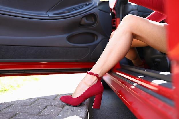 Jambe de femme en chaussures rouges près de voiture