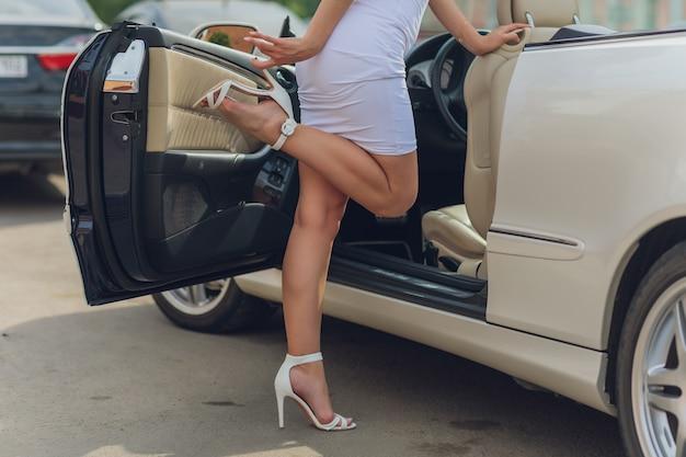 Jambe de femme de conducteur en voiture avec porte ouverte