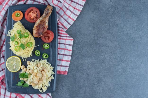Jambe grillée, spaghetti et riz sur planche sombre.