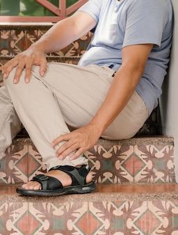 La jambe de l'homme est douloureuse et engourdie, épuisée, picotements, effet secondaire du syndrome de guillainbarre du vaccin covid
