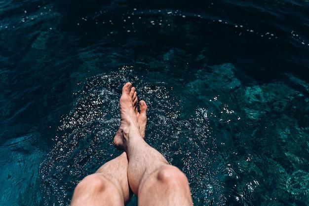 La jambe de l'homme suspendue à la jetée pieds nus avec le fond de la mer