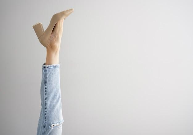 La jambe d'une jeune femme en jeans et chaussures sur fond gris, place pour le texte.