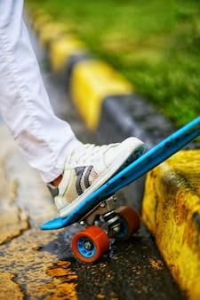 La jambe soutient la planche à roulettes sur le plan rapproché de trottoir