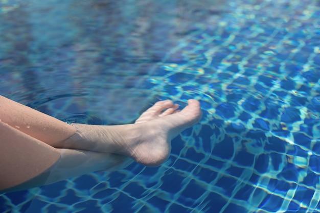 Jambes d'un adolescent sous l'eau dans la piscine repos d'été