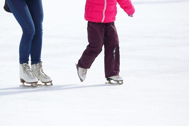 Les jambes d'un adulte et d'un enfant patinant sur la patinoire