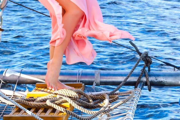 Jambes aux pieds nus d'une femme vêtue d'une robe romantique debout à bord du yacht parmi les engins des navires