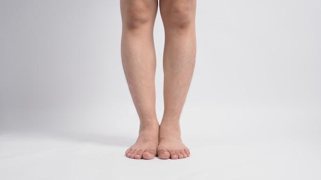 Jambes aux pieds nus masculins asiatiques isolés sur fond blanc.