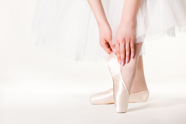 Jambes de ballerine femme en tutu blanc et pointes sur fond blanc