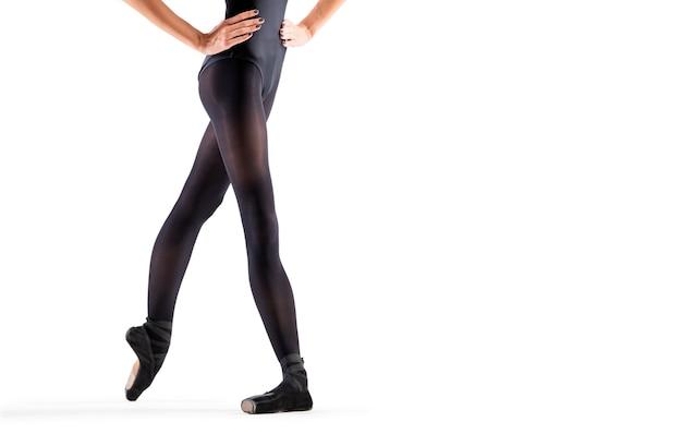 Jambes de ballerine en pointes noires et justaucorps debout isolés sur fond blanc
