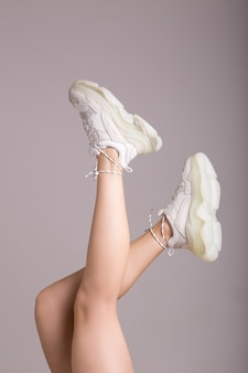 Jambes en baskets blanches