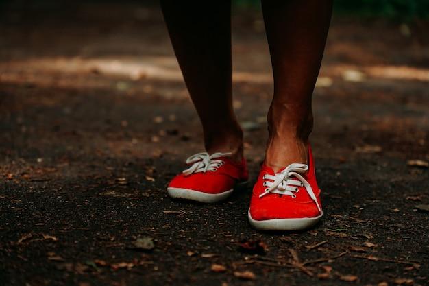 Jambes en baskets rouges sur un chemin d'automne dans le parc. pieds en cuir noir. sport en forêt d'été