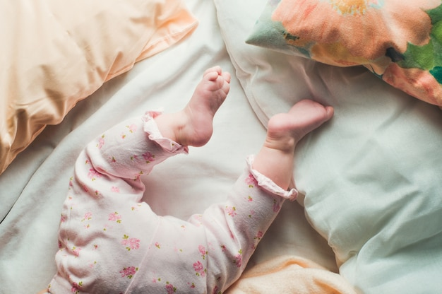 Jambes de bébé dans le lit