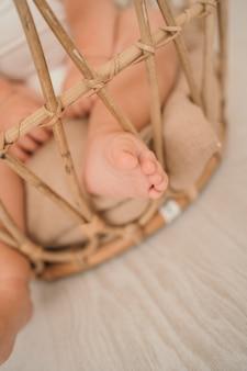Jambes de bébé gros plan une petite jambe d'enfant dans un panier photo verticale d'un petit espace d'enfant pour le texte et...
