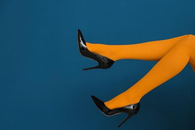 Jambes de belle femme dans des chaussures élégantes sur la couleur