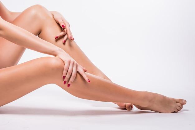 Jambes de belle femme avec une peau blanche lisse isolé sur blanc