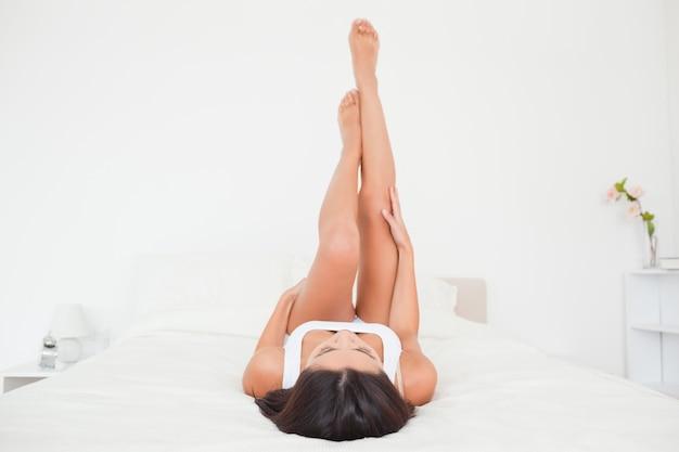 Jambes de belle femme soulevées haut sur le lit