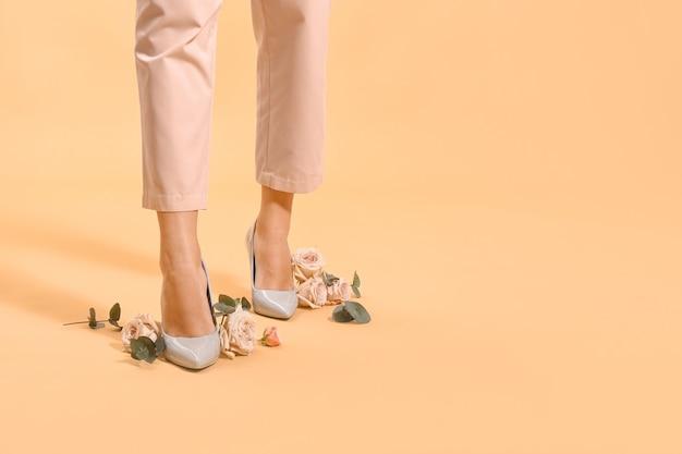 Jambes de la belle jeune femme avec des fleurs roses sur la surface de couleur