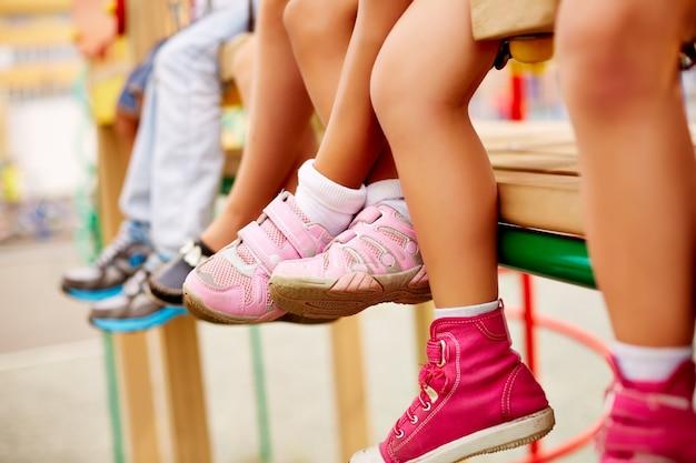 Jambes de camarades de classe assis sur le terrain de jeu