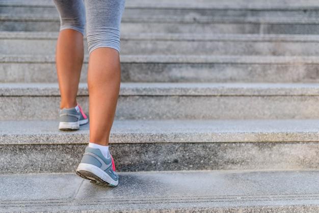 Jambes et chaussures d'un jogger courant dans un escalier