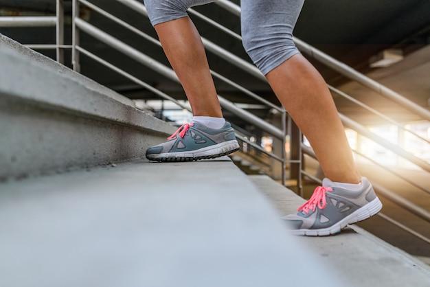 Jambes et chaussures d'un jogger en courant un escalier