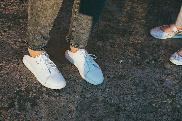Jambes et chaussures de mère et de fille sur l'asphalte, seulement les pieds