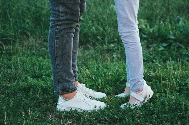 Jambes et chaussures de mère et de fille sur l'herbe, seulement les pieds