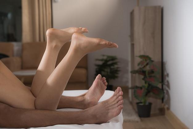 Jambes de couple ayant des relations sexuelles sur le lit