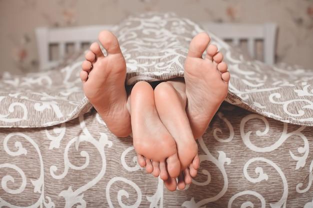Des jambes de couple sortent de sous une couverture