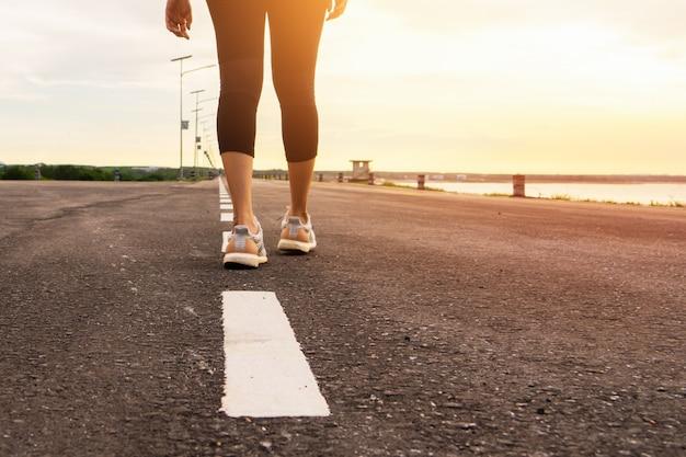 Jambes de coureur féminin sport prêt à courir sur sentier forestier