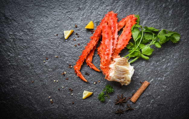 Jambes de crabe royal d'alaska cuites avec des herbes et des épices au persil citron sur des fruits de mer au crabe rouge foncé
