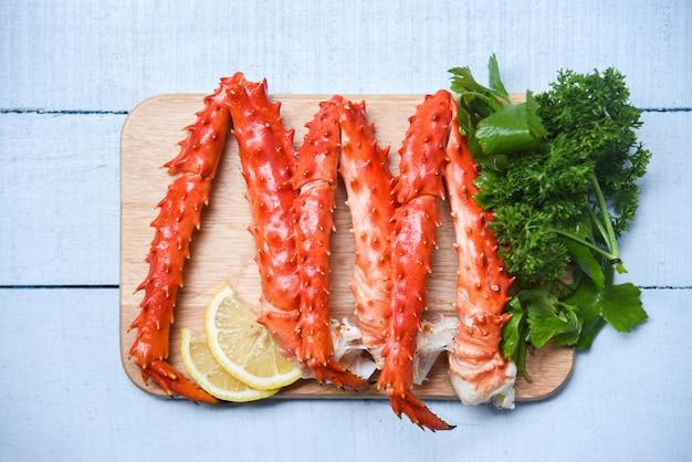 Jambes de crabe royal d'alaska cuites sur une planche à découper en bois avec persil citron