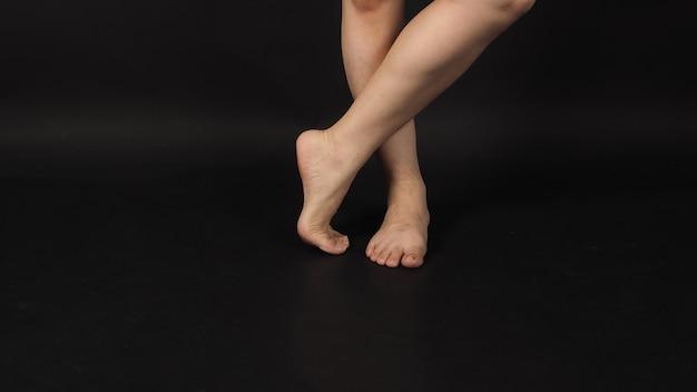 Les jambes croisées mâles asiatiques et pieds nus sont isolées sur fond noir