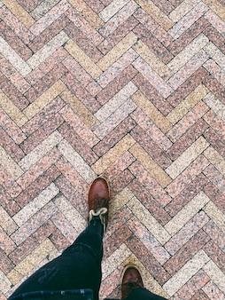 Jambes en cuir marron bottes marchant sur fond de granit humide sous forme de rectangles