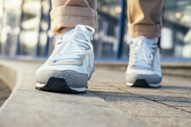 Les jambes dans un pantalon beige et des baskets blanches sont sur le trottoir