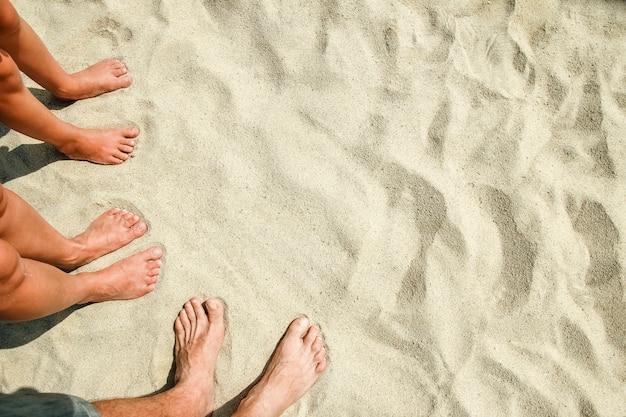 Les jambes dans le sable de la mer