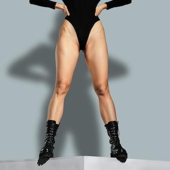 Jambes de danseuse musculaire posant dans des bottes rugueuses