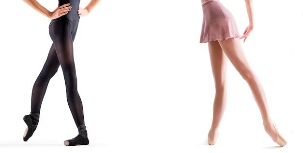 Jambes de deux ballerines en chaussons de pointe noirs et roses et justaucorps debout isolés sur fond blanc