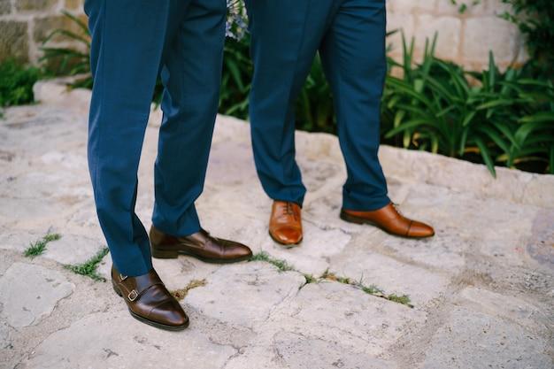 Les jambes de deux hommes debout sur une route pavée en gros plan le marié et son meilleur homme pendant la