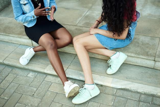 Jambes de deux jeunes femmes. conversation de copines dans la rue, concept. sans visage.