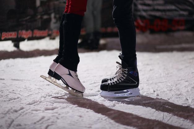 Jambes du couple de baisers amoureux sur des patins.