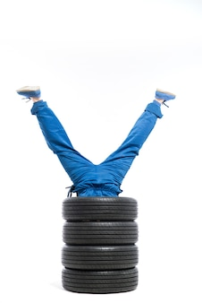 Les jambes du travailleur sortent du tas de pneus