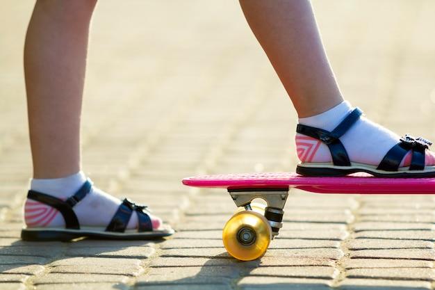 Jambes d'enfant sur planche à roulettes rose en plastique