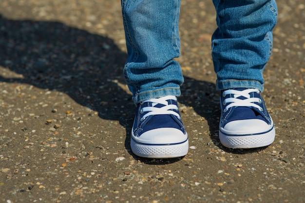 Des jambes d'enfants en baskets en jean sont accrochées au fond du trottoir.