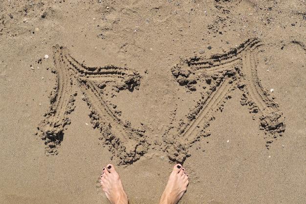 Jambes féminines aux pieds nus avec deux flèches dessinées dans le sable dans des directions différentes.