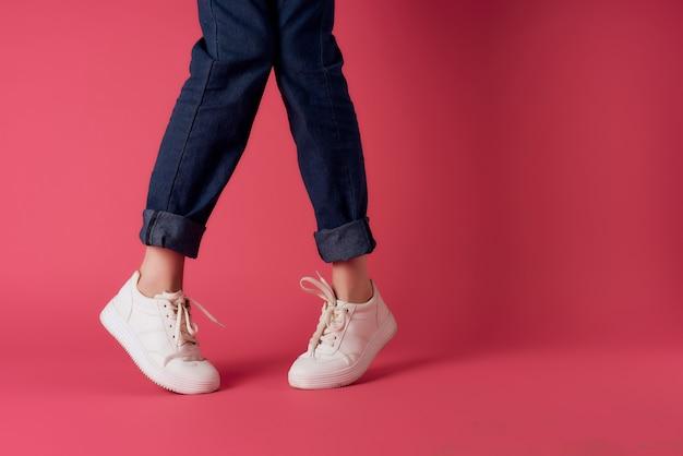 Jambes féminines en baskets blanches à la mode posant sur fond rose