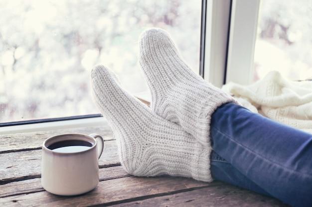 Jambes féminines et boisson chaude sur le rebord de la fenêtre