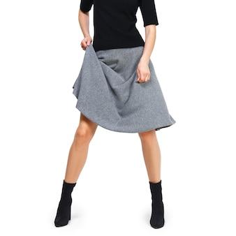 Jambes féminines en bottes avec jupe relevée, vêtements tricotés