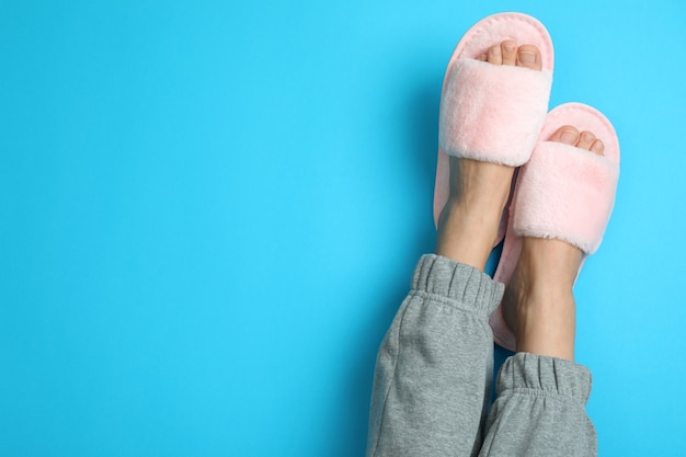 Jambes féminines en chaussons roses sur fond bleu