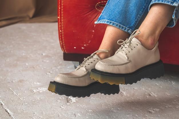 Jambes féminines avec des chaussures en cuir. gros plan de baskets chez les adolescentes. teen girl sitting on old leather chair in studio, photo d'arrière-plan en béton